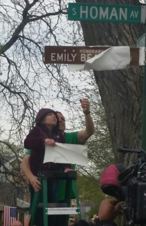 Emily Beazely and her father Ed unveil an honorary street sign for her April 24.