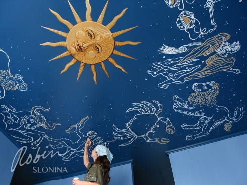 Robin Slonina working on one of her murals
