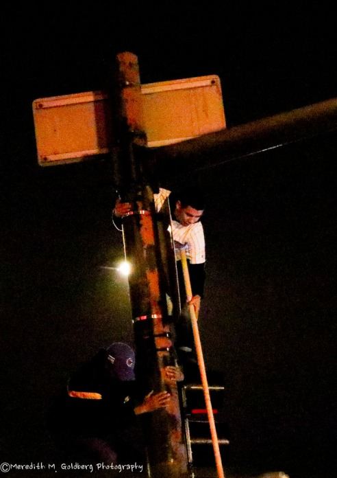Fans climbing the lightpole at Addison and Clark during the 8th to wave the W flag.