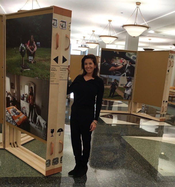 """Jane Saks in front of her """"Working In America"""" exhibit at the Harold Washington Library."""