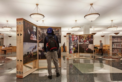 "A library patron looking at the ""Working in America"" exhibit. Photo by Tom Harris"